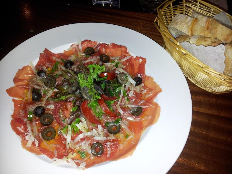 Rindercarpaccio mit Olivenöl, Oliven und Parmesan, dazu Baguette
